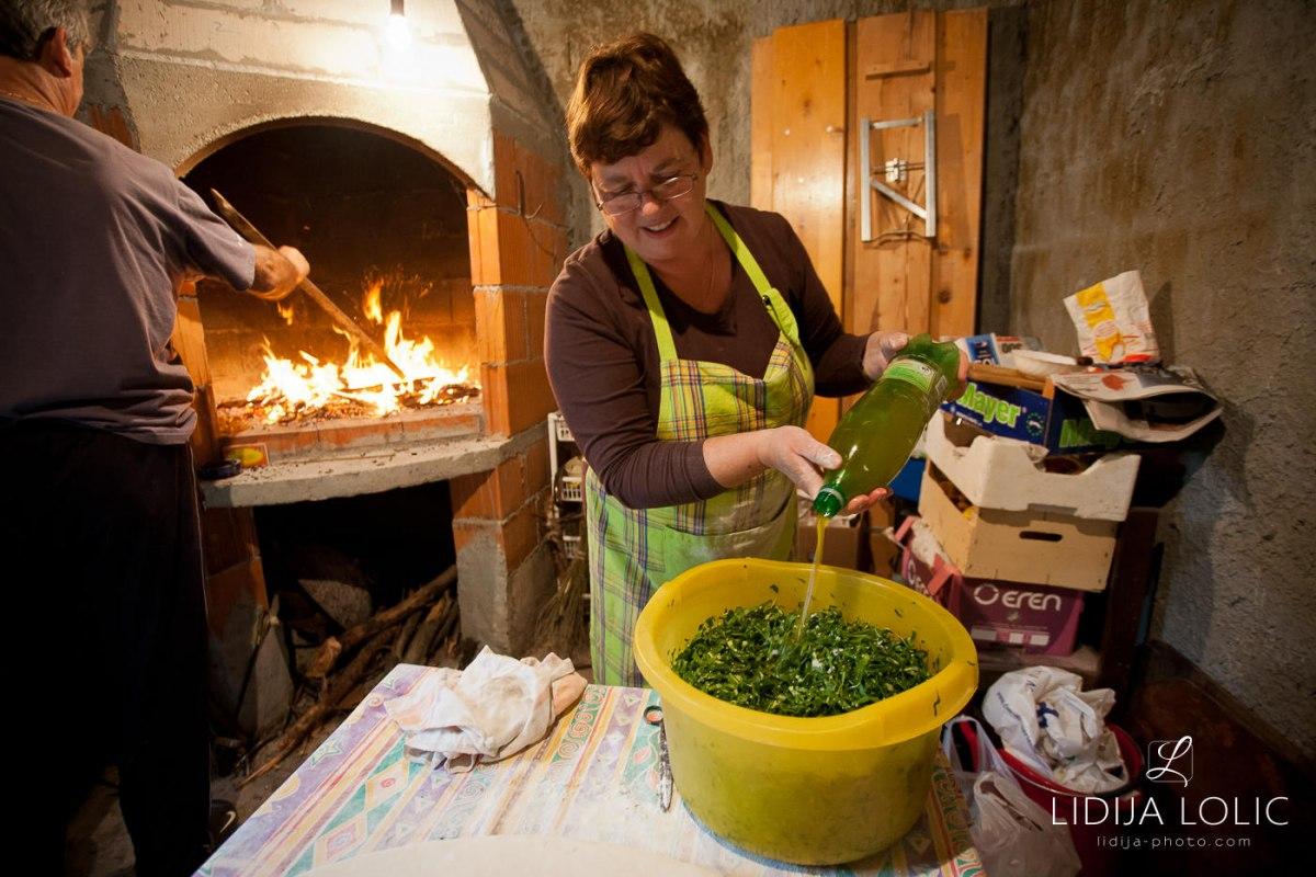 Adding olive oil to soparnik